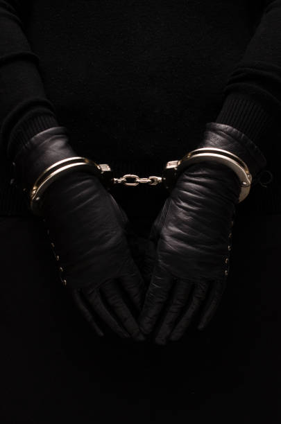 Silver handcuffs leather black gloves, concept Silver handcuffs leather black gloves, concept arrestment stock pictures, royalty-free photos & images
