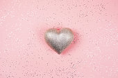 Silver heart on pink background with sparkles.