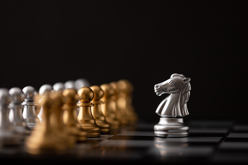 silver hores is the leader of the chess in the game on board with black background.