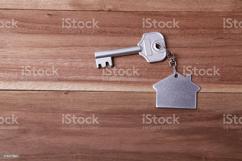 house key. silver house and key chain on a wood table stock photo