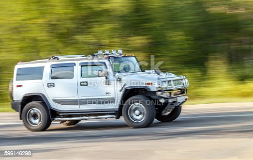 Russia, Irkutsk - August 20, 2015: Silver big Hummer car rides up the road at high speed.