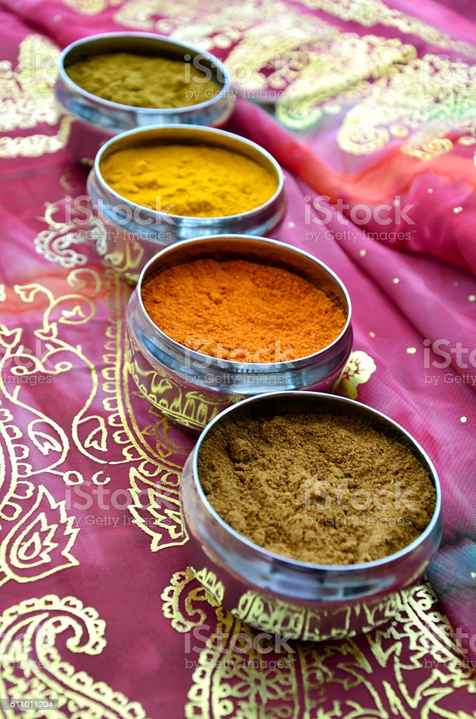 Silver Indian Spice Pots on Pink and Gold Paisley Sari stock photo