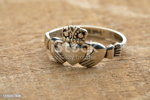 Silver Irish Claddagh ring on wooden background