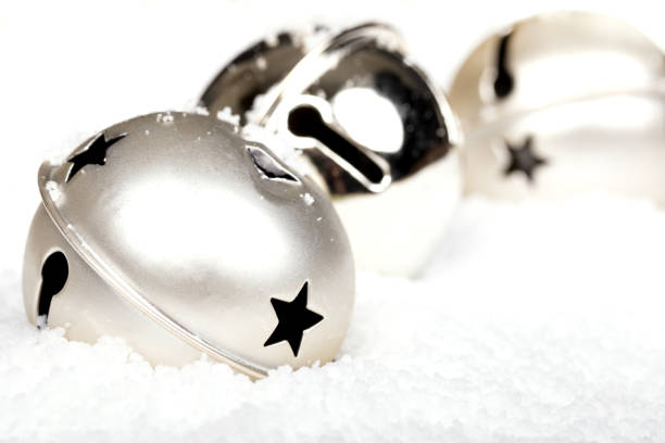 Silver jingle bells in the snow stock photo