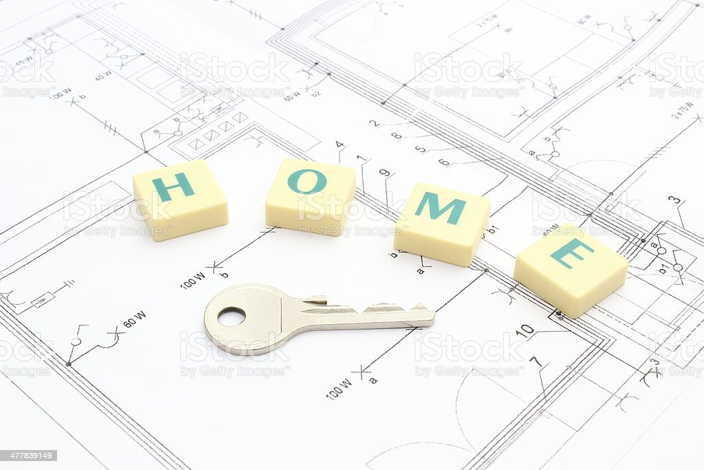Silver key and word 'home' on the housing plan royalty-free stock photo