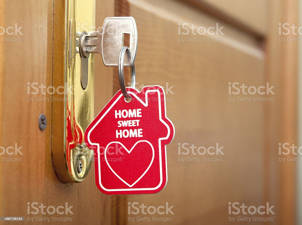 A silver key in a door lock with a red keychain attached stock photo