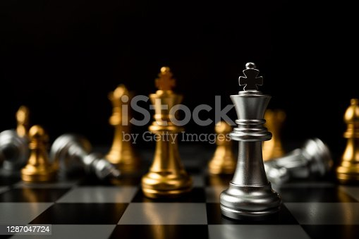 Silver King chess standing in front of other chess, Concept of a leader must have courage and challenge in the competition, leadership and business vision for a win in business games