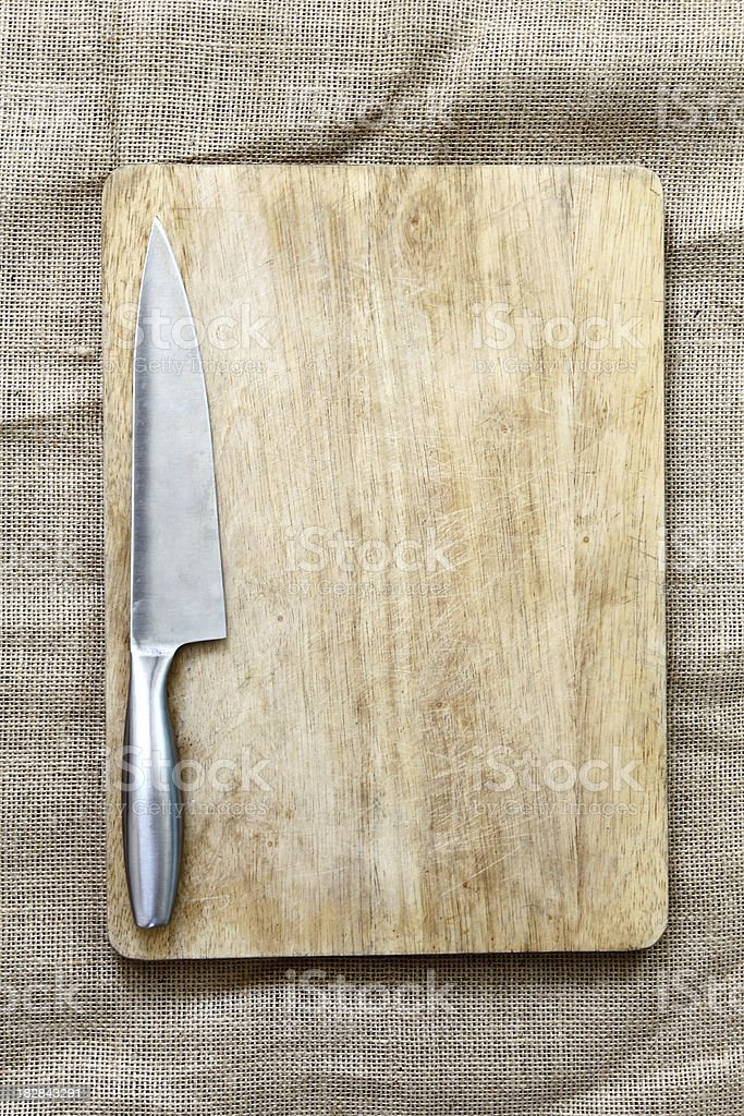 Silver knife resting on a wooden cutting board. stock photo