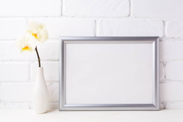 Silver landscape frame mockup with soft yellow orchid in vase stock photo