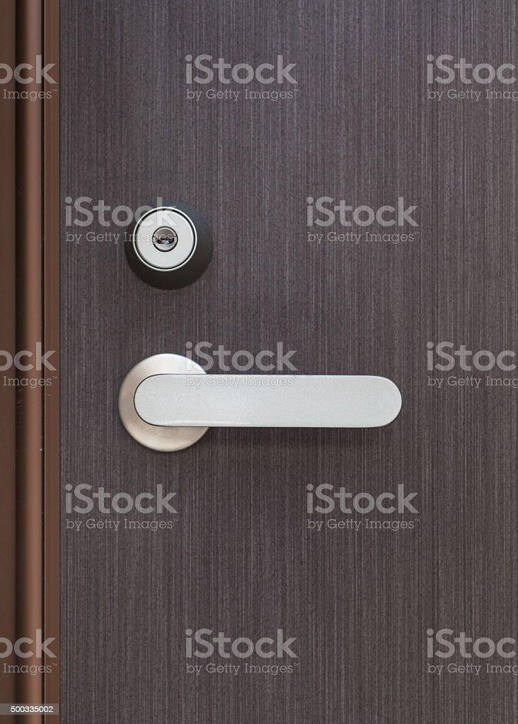 Silver metal door handle and brown wood door stock photo