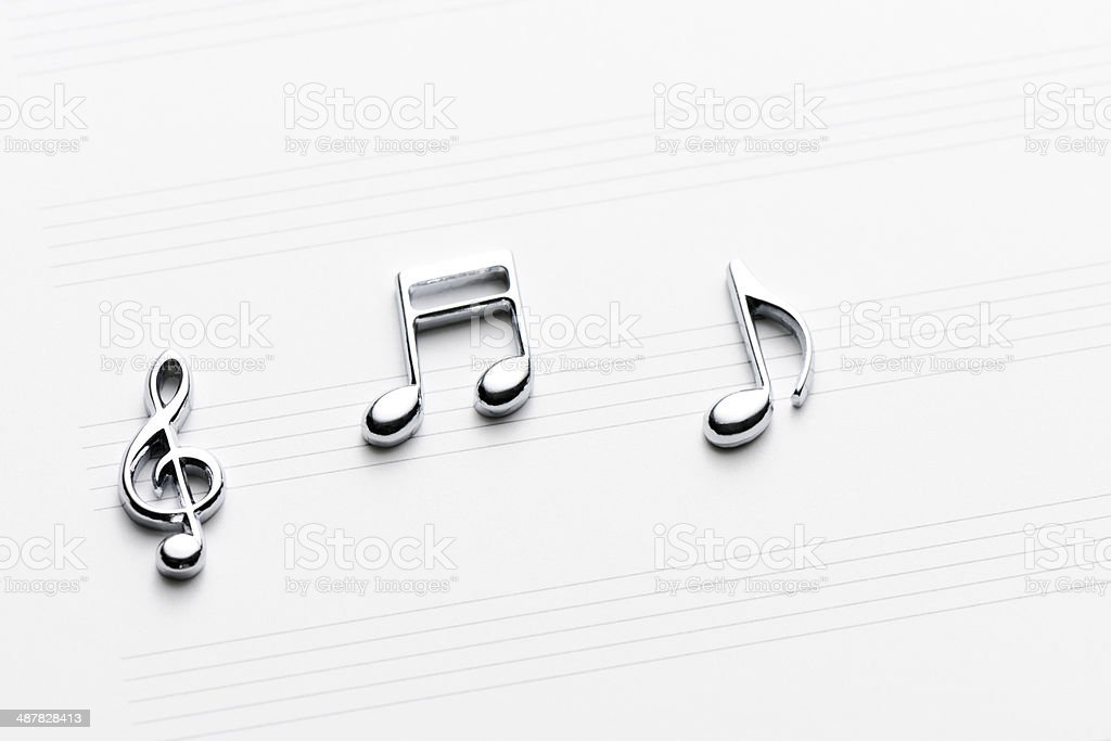 Silver metal musical note with sheet music royalty-free stock photo