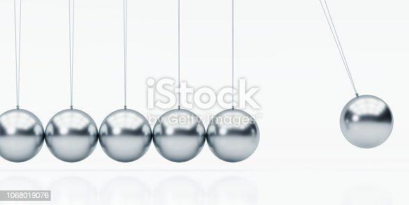 Silver metal Newton's Cradle isolated on white background. Horizontal composition with clipping path and copy space.