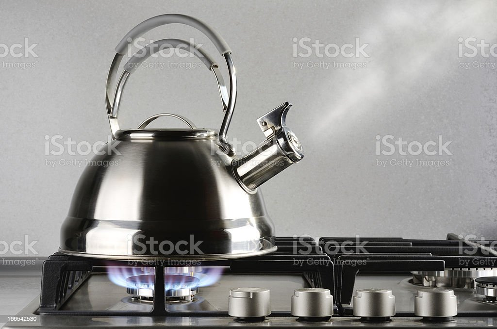 Silver metal tea kettle blowing steam as reaches boiling stock photo