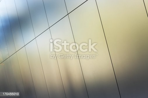 Silver metallic building wall panels reflect a pattern and color in muted sunlight.  Phoenix, Arizona, 2013.
