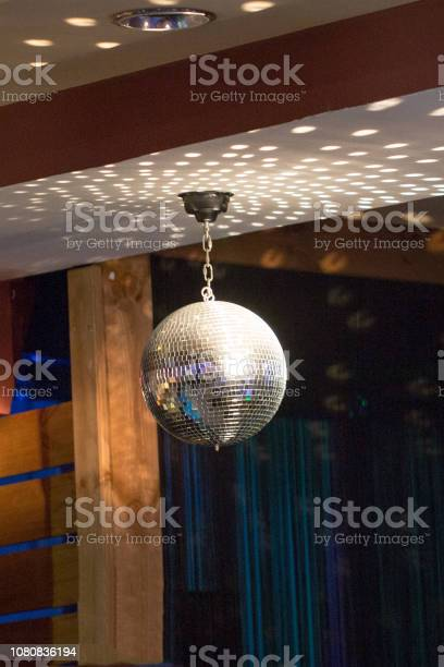 Silver mirror disco ball in the rays of the spotlights