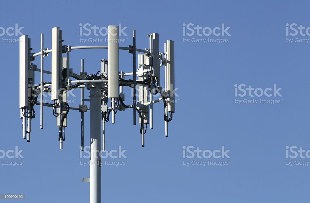 A silver mobile phone tower in the blue sky royalty-free stock photo