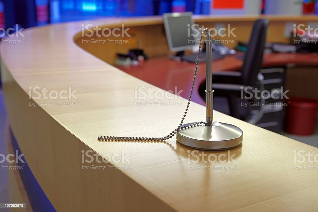 Silver pen attached to a front desk stock photo