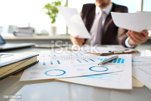 istock Silver pen lie at important paper on table in office 1061035038