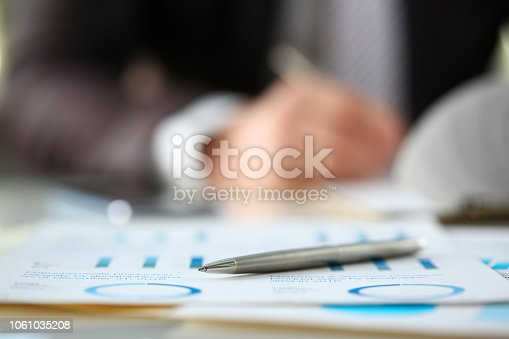 istock Silver pen lie at important paper on table in office 1061035208