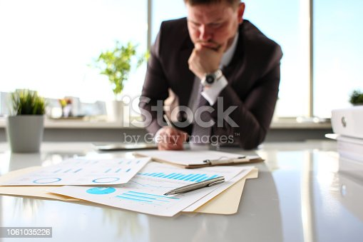 istock Silver pen lie at important paper on table in office 1061035226