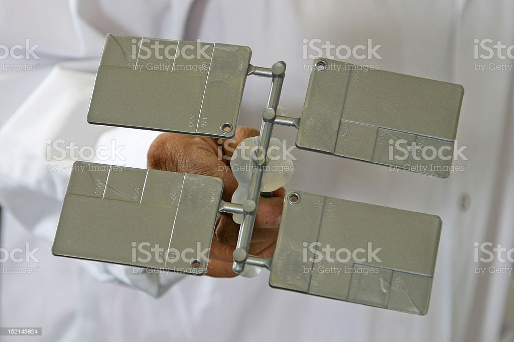 silver plastic injection molding part held by operator stock photo