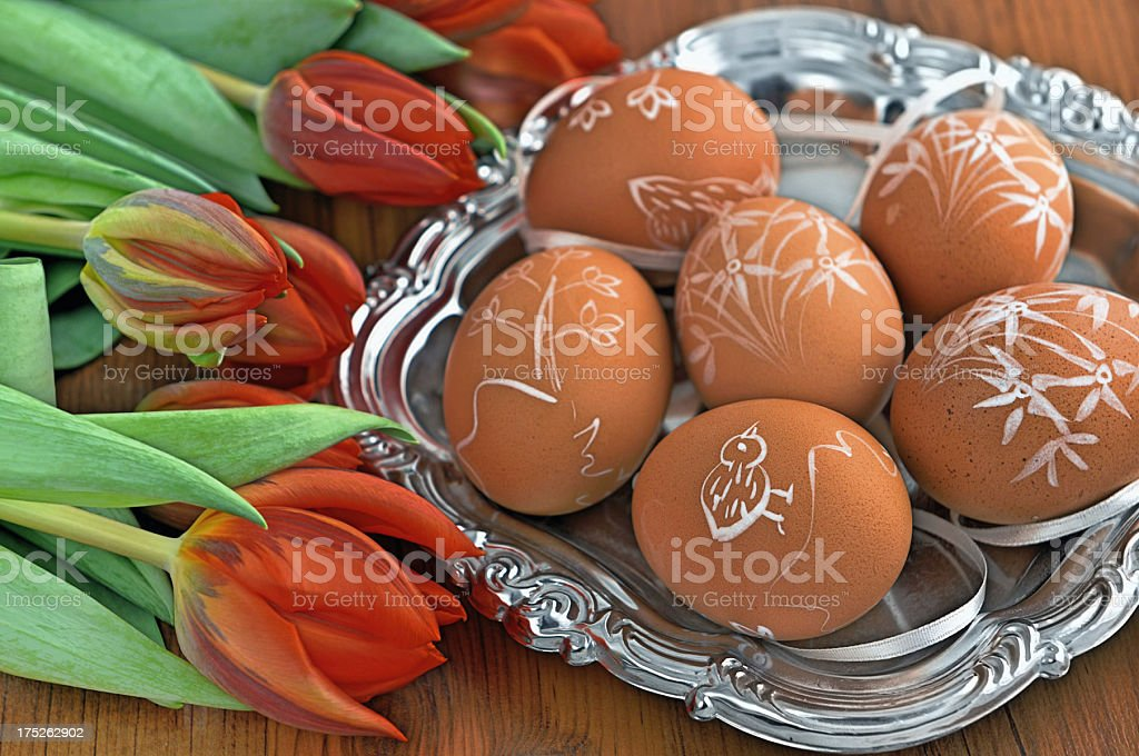 silver plate with Easter eggs and red tulip table royalty-free stock photo