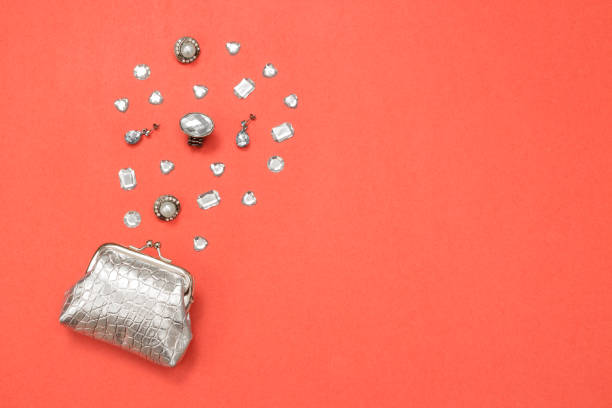 Silver purse, gems and jewelry on pink background stock photo