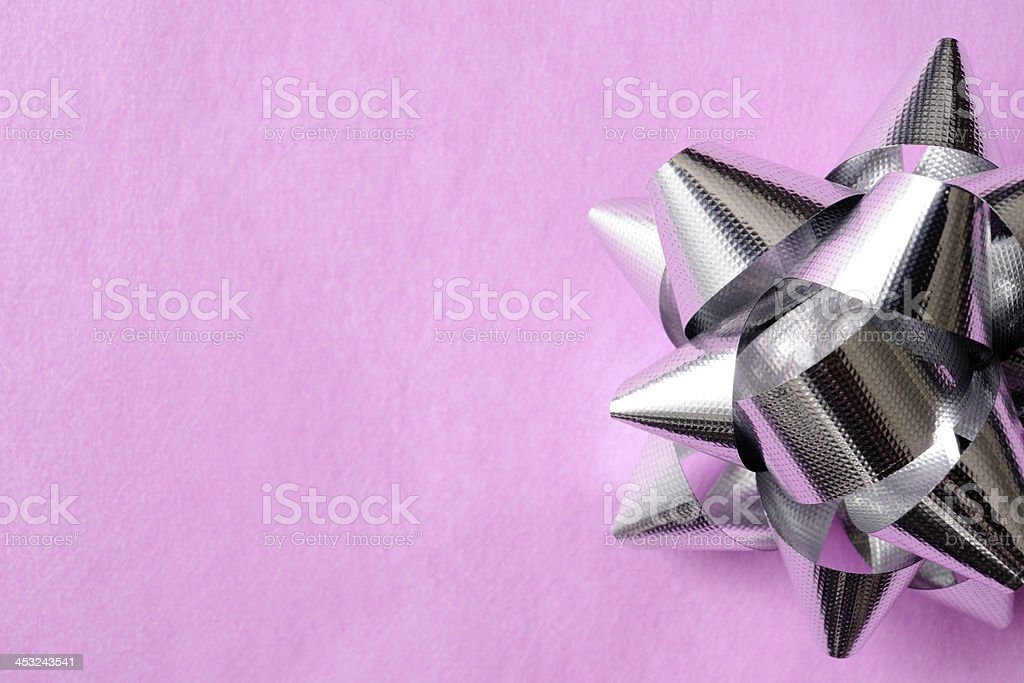 Silver ribbon on purple wrapping paper with copy space royalty-free stock photo