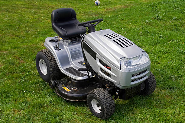 silver riding lawn mower sitting on lawn - riding lawn mower stock photos and pictures