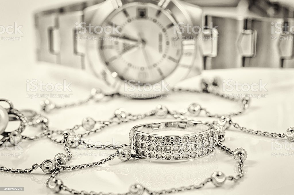 Silver ring and chain on the background of watches stock photo