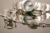 Silver rings and silver chain on background of women's watch