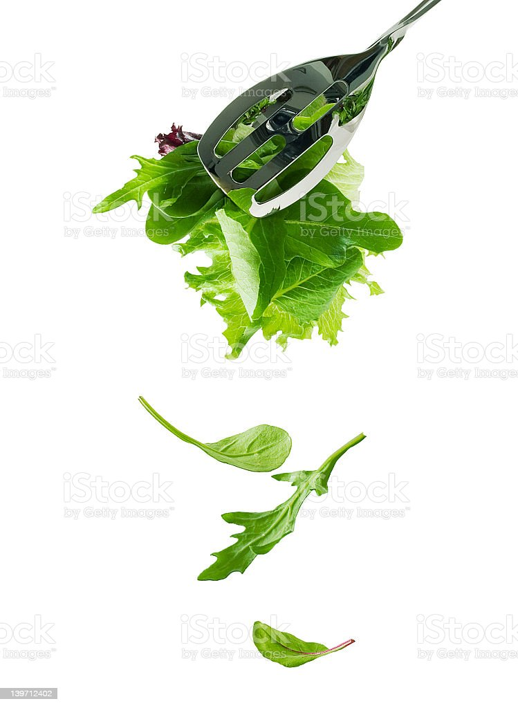 Silver salad tongs with salad leaves cascading downwards stock photo
