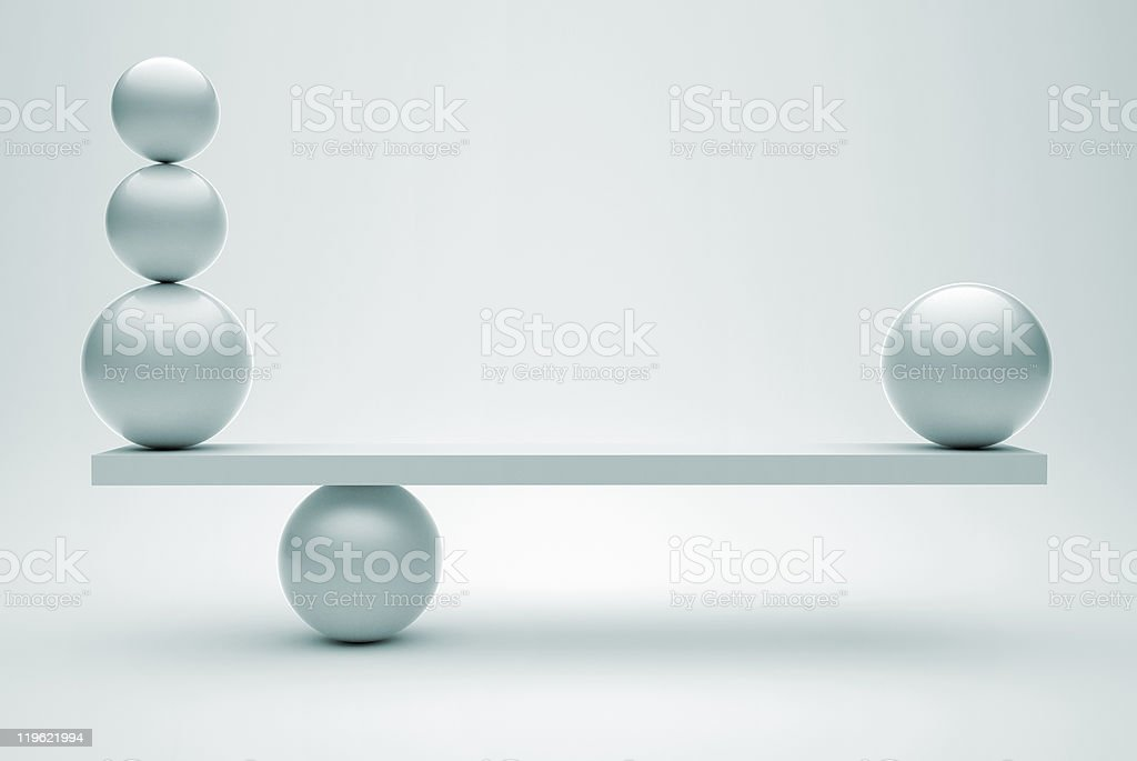 Silver scale with one ball on right and three balls on left stock photo