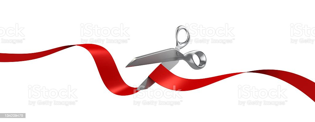 Silver scissors cutting red ribbon on white background stock photo