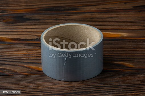 istock Silver Scotch tape on a wooden table. 1250276555