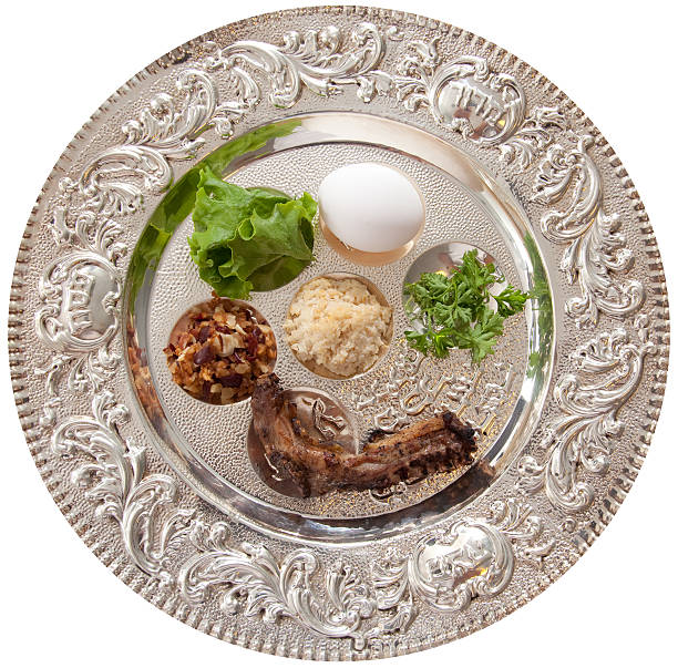 Silver Sedar plate with egg, parsley, lettuce, meat Traditional symbols on a seder plate for the Jewish festival of Passover. seder plate stock pictures, royalty-free photos & images