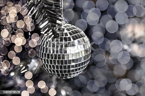 istock Silver shiny disco toy ball on Christmas tree with blurred lights. 1083979528