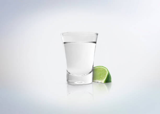 Silver shot of tequila. Alcoholic distilled beverage with slice of lemon / lime on the side. Isolated on white background. tequila shot stock pictures, royalty-free photos & images
