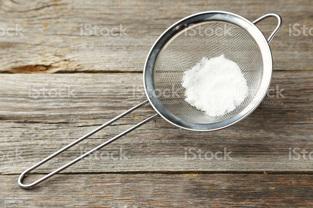Silver sieve with flour on grey wooden background stock photo