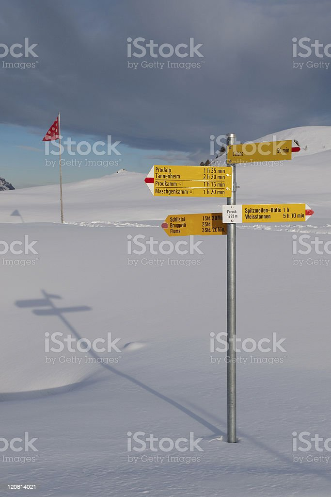 Silver sign post with yellow signs in the snow by a red flag stock photo