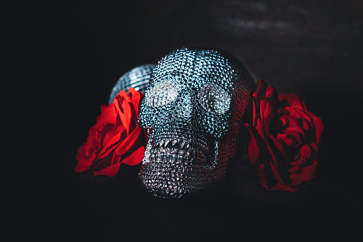 Shiny sparkling bright skull candy with red rose and a disco ball. Party invitation for Halloween. Close up, selective focus.