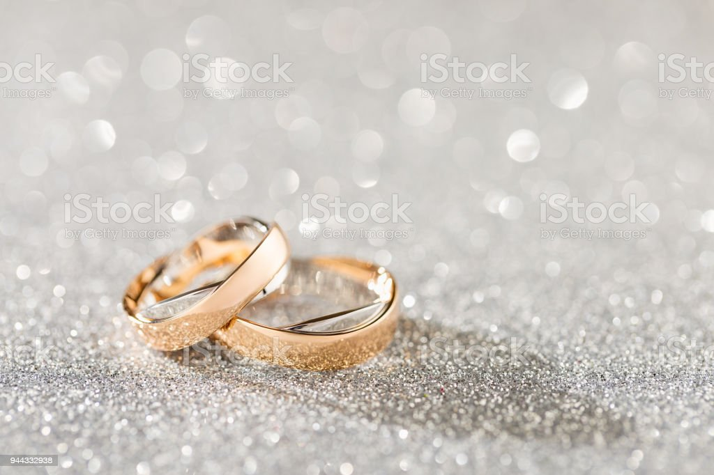 Silver sparkling glitter bokeh background with golden wedding rings stock photo