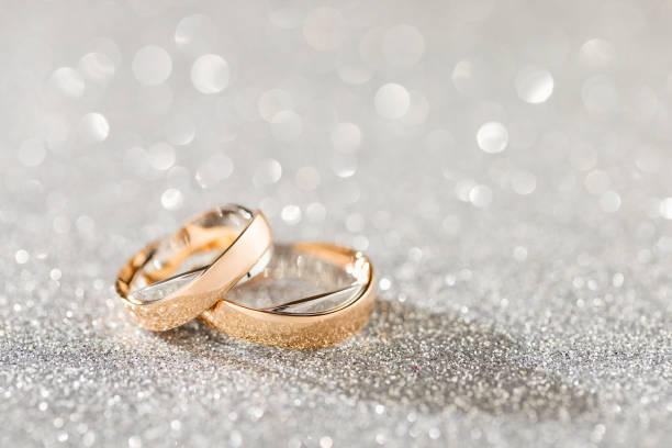 Silver sparkling glitter bokeh background with golden wedding rings