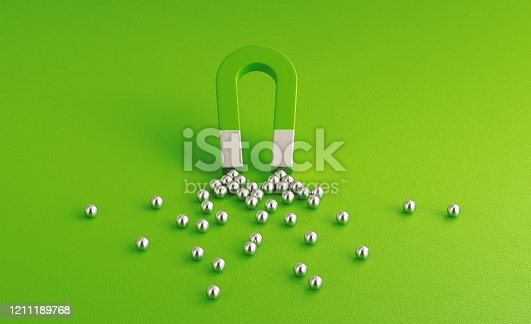 Silver spheres gravitated towards a green magnet on green background. Horizontal composition with copy space. Digital marketing concept.