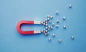 Silver spheres gravitated towards a red magnet on blue background. Horizontal composition with copy space. Digital marketing concept.