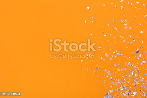 Silver glitter on a bright orange background with place for text, festive backdrop