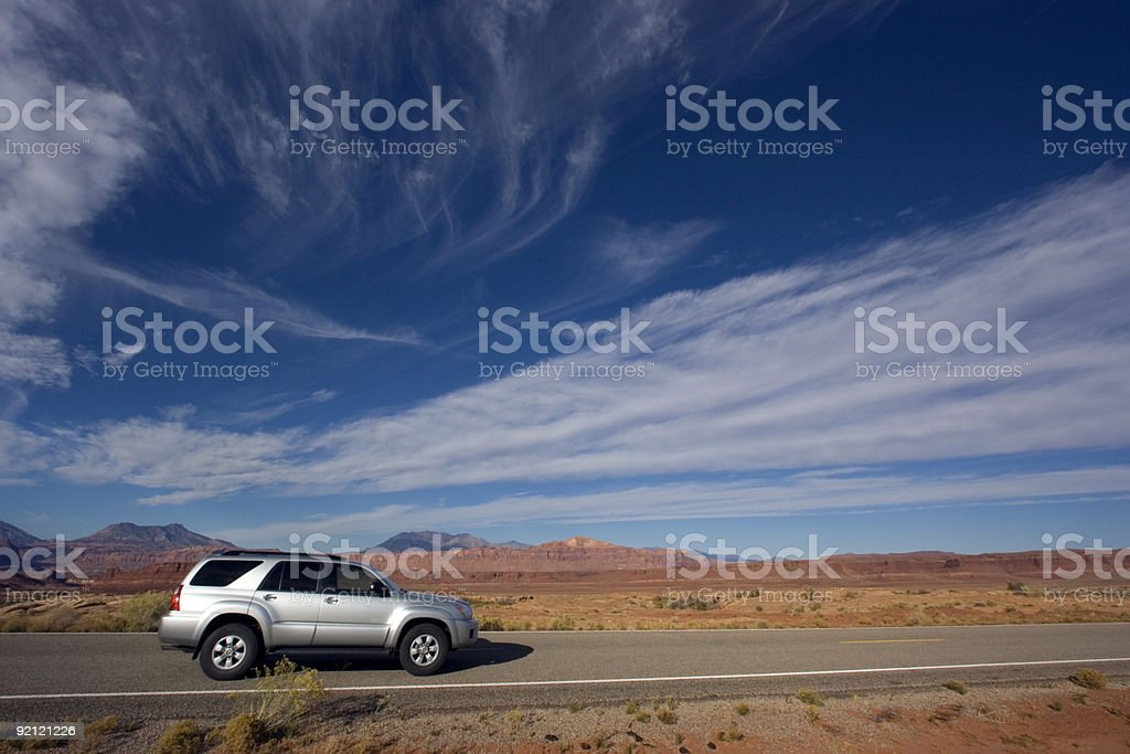 Silver SUV driving down a deserted road in Utah  stock photo