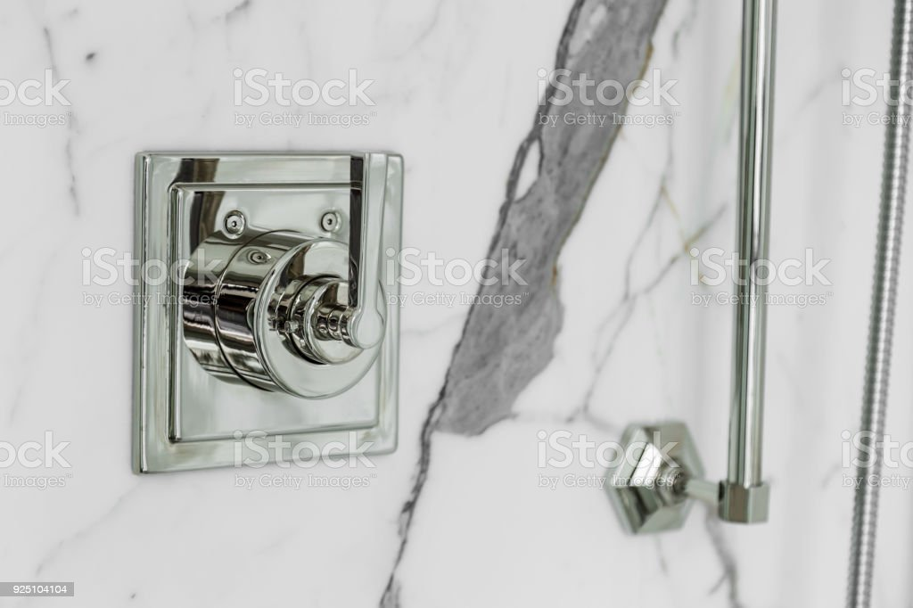 silver tab for shower in white marble wall interior design concept stock photo
