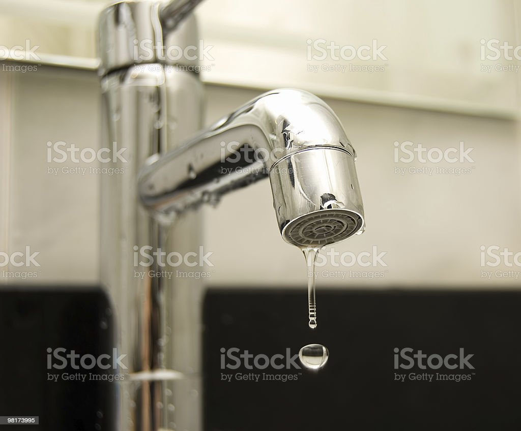 A silver tap with a droplet of water falling out royalty-free stock photo