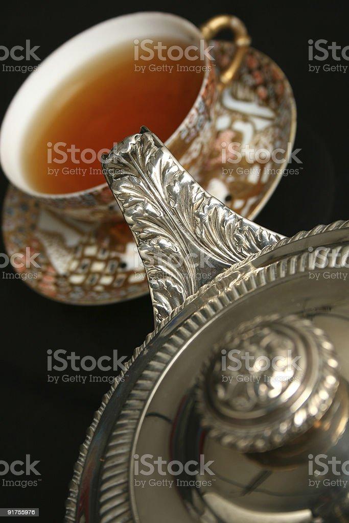 Silver teapot pouring tea royalty-free stock photo